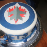 Winnipeg Jets Birthday Cake   a 10in cake made with the Winnipeg jets Logo and a 3D figurine of the birthday boy wearing the Jets Jersey