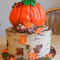 Fall Wonderland Pumpkin Spice cake decorated with crusting cream cheese icing. The pumpkin is covered in Modelling chocolate. All other details are either...