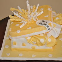 Yellow Gift Box marble cake with chocolate creamceese frosting and vanilla butter cream and covered in mmf. The lid and all the decorations are made with...