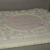 Simple Christening Cake Covered in white buttercream with pale pink gumpaste flowers and lettering