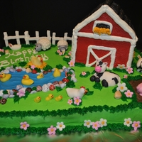 Kinsley And Kamden's Birthday Cake I made this cake for family members. Buttercream icing with fondant animals and flowers. All hand made and edible!