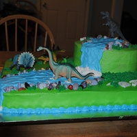 Dinosaur Brithday Birthday Cake for a child. Rocks are chocolate candy, bones and eggs are fondant. Dinosaurs are not hand made.