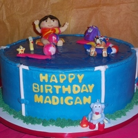 Dora The Explorer   Marble cake, vanilla buttercream, water is made with tinted piping gel. fondant/gumpaste figures.