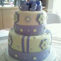 Baby Shower Purple And Green Yellow cake with raspberry filling, frosted in a raspberry buttercream covered and decorated with fondant.