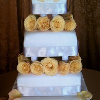Fall Wedding Cake 4-tier wedding cake with antique white fondant and real orange roses. The gold accents are gold colored fondant, then sprayed gold with...