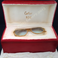 Cartier Glasses Box was cake with a fondant covered sugar lid. Glasses were made with isomalt and trimmed with gumpaste and painted gold.