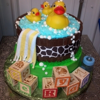 "Rubber Ducky Baby Shower Cake Rubber Ducky baby shower cake. 8 inch and 10 inch stacked cake. The ""barrel"" is kit kat bars turned backwards with a ribbon..."