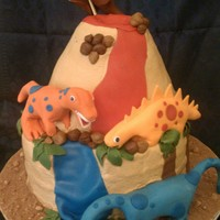 Dinosaur Cake Made this for a little guys 4th birthday. Top volcano cake is carved red velvet with cream cheese filling, bottom tier is chocolate chip...