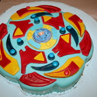 Bey Blade Cake Truffle and chocolate butter icing layers, covered with fondant..with an edible print of beyblade in the centre