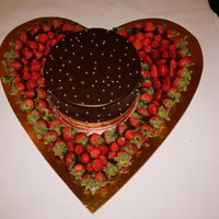 Strawberry And Truffle Heart strawberry half dipped in chocolate and arranged around a decadent chocolate cake..