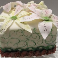 Lilly Cake 6 inch square cake covered in buttercream fondant with Lilly-type flowers on top made with gumpaste. Sides of the cake are decorated with...