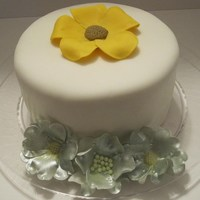 6 Inch Round Yellow cake with buttercream frosting and MMF decorated with gumpaste flowers. Silver flowers airbrushed and then a little petal dust added...