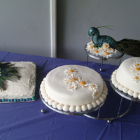 Peacock/daisy Wedding Layer cakes with fondant daisies, sheet cakes with peacock feather/daisy decor, fondant sculpted peacock.