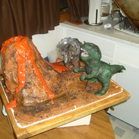 Dinosaur Cake Sheet cake with cake volcano, dinosaurs sculpted from fondant.