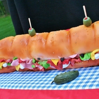 Sub Sandwich Cake! This cake was for an outdoor summer party! Airbrushed for detail, made of all cake, including the added pickle and olives for garnish!