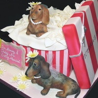 Victoria's Secret Gift Box With Pups.  This is a bridal shower cake made of maple cake, filled with pecan pie filling, maple SMBC and covered with vanilla MMF. The dogs are...
