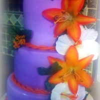 Purple And Orange Destination Wedding Cake Orange and purple wedding cake with orange lilies and white hibiscus flowers adorning it. Vanilla and chocolate cake wrapped in purple MMF...