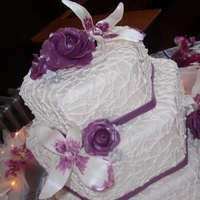 Orchid And Rose Wedding Cake I made roses and orchids and hand painted them and did a lace pattern on the cake. The shape is a hexagon!