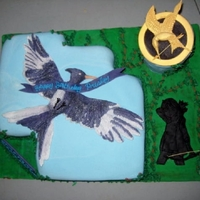 Hungergames choc cake covered in fondant with a 2D of the Mockingjay. Pedestal is rice krispie treat covered in fondant. the gold pin is also fondant....
