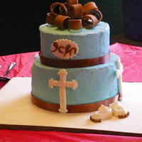 Twp-Tiered Baptism Cake Top tier is almond pound cake filled with chocolate ganache. Bottom tier is chocolate-cinnamon cake filled with rasberry filling. Iced with...