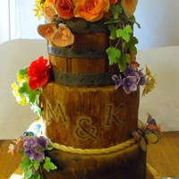 Wood Stumps And Flower Basket wood textured fondant covered wedding cake with sugar flowers, hummingbirds and butterflies. Vanilla cake with white chocolate fondant,...