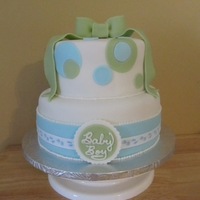 Blue And Green Baby Shower Fondant blue and green baby shower cake with fondant bow topper and real ribbon accents.