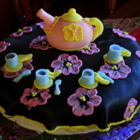 This Is A Yellow Pudding Cake Covered With A Black Fondant Tablecloth The Tea Set Is Also All Fondant This is a yellow pudding cake covered with a black fondant tablecloth. The tea set is also all fondant.