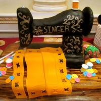 Singer Sewing Machine The sewing machine is RKT covered in black fondant and hand painted with gold pearl dust and vodka. The table is chocolate cake with a...