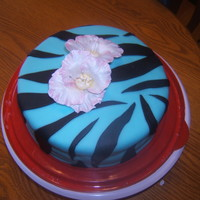 Blue, Zebra Print Topped With Flowers.  Made this for practice, left the cake out of the fridge a bit to long and the sides sagged, I tried to smooth them out but it was to hard...