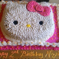 Hello Kitty Cake Used Wilton Hello kitty pan. Hello Kitty is on top of 1/2 sheet sized cake. All cake is iced with cream cheese butter cream frosting!