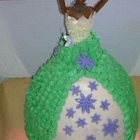 Princess Tiana Doll Cake Vanilla cake iced with cream cheese buttercream frosting. Accented with fondant daisy flower cut outs. Used Wilton doll cake pan along with...