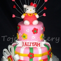 "Hello Kitty A two-tier chocolate cake covered in baby pink fondant (size: 6"" and 4"") accented with white bows and colorful flowers with small..."