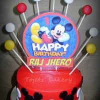 "Mickey Mouse Themed Cake A 6""x3"" chocolate cake in red buttercream with black mickey mouse faces and white polka dots all represented by our all time..."