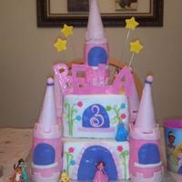 Princess Castle Cake covered in fondant. Tiers made of rice krispies and cones out of ice cream cones. All fondant decor except for the sugar flowers and...