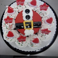 Santa's Belly 5 inch cake made to look like Santa's belly surrounded by cupcakes