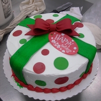 Christmas Gift 10 inch round cake with buttercream base ice and ribbon, gumpaste bow, and fondant dots.