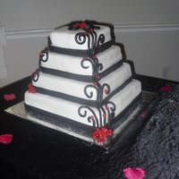 Scrolled Wedding Cake   Four tier wedding cake with scroll work and red flowers