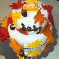 Fall Themed Baby Shower Cake red yellow orange gumpaste leaves covering two tier mmf covered cake. Baby made from first impression mold, painted hair and details with...