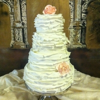 Ruffled White Wedding Cake Messy ruffles match the brides dress. Soft peach roses to add a touch of color. Cake made using MMF. Gumpaste flowers