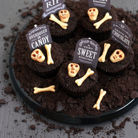"Spooky Graveyard Oreo Cupcakes Vanilla-based Oreo Cupcakes with ganache and cookie crumb ""dirt"" topping plus fondant bones and paper tombstone topper. The..."