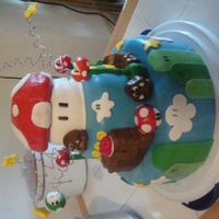 "Mario Brothers The mushroom top is rice krispy treats, the base is a 4"" cake. All the decorations are MMF."