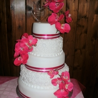 Pink Orchids Wedding Cake  WEDDING CAKE ~ FIVE TIERS OF FRUIT, VANILLA, STRAWBERRY, VANILLA, AND CHOCOLATE CAKE DECORATED IN WHITE ICING, WITH HAND PIPED ROYAL ICING...