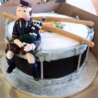 Pipes And Drums Band Round cake covered in fondant,Sides airbrushed black.Photo image placed on top of drumGumpaste drumsticksFondant piper