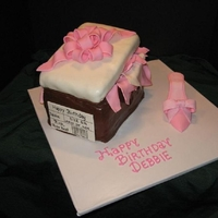 "Shoe Box Cake With Pink High Heel A pink high heel shoe with embossed ribbon next to a chocolate fondant covered shoe box. The lid is a 1"" cake tilted with gum paste..."