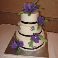 Deep Purple And Lavender Blossoms Compliment This Cake The Black Ribbon Set Off The Flowers Also The Bottom Layer Is Chocolate Filled Wi Deep purple and lavender blossoms compliment this cake. The black ribbon set off the flowers also. The bottom layer is chocolate filled...
