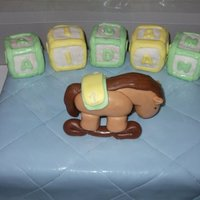 Baby Blanket Cake With Rocking Horse Baby blanket design with fondant rocking horse and rice cereal letter blocks.