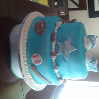 Sports Themed Blue Cake This is white cake with strawberry mousse. All decorations are made with fondant and gumpaste.