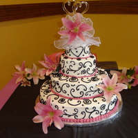 Black And Fusia Wedding Cake 14, 10, 6, & 4 inch round cakes. Frosted and scrolling done all with butter cream!