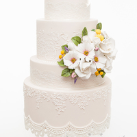 Vintage Soft Peach Wedding Cake A peach dummy cake made in a vintage style with sugar flowers and edible lace. The flowers are a mix of Roses, Cosmos as well as some...