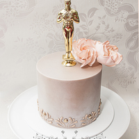 Oscar Themed Birthday Cake An Oscar themed birthday cake in shimmering champagne and gold. Sugar roses and piped royal icing design on the side. The only thing...